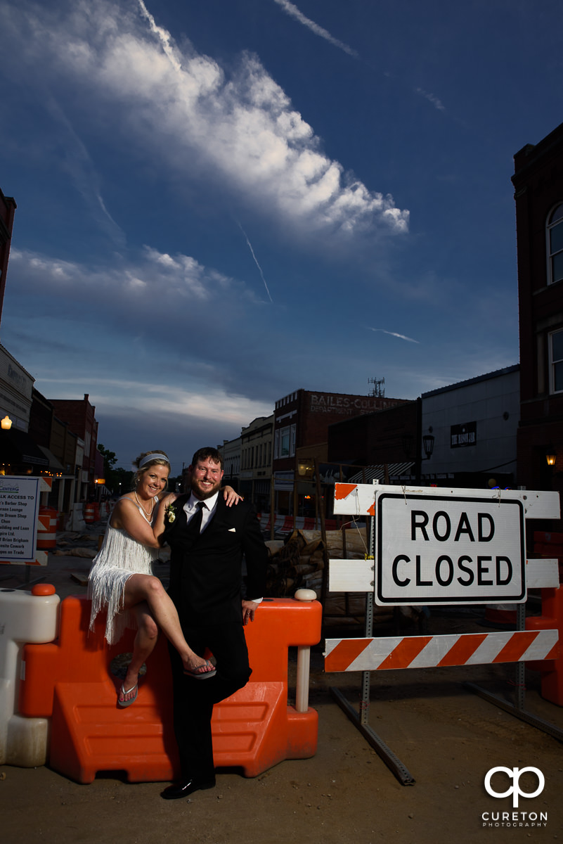 Bride and groom sitting in the middle of road construction outside of their Grace Hall wedding reception in Greer, SC.