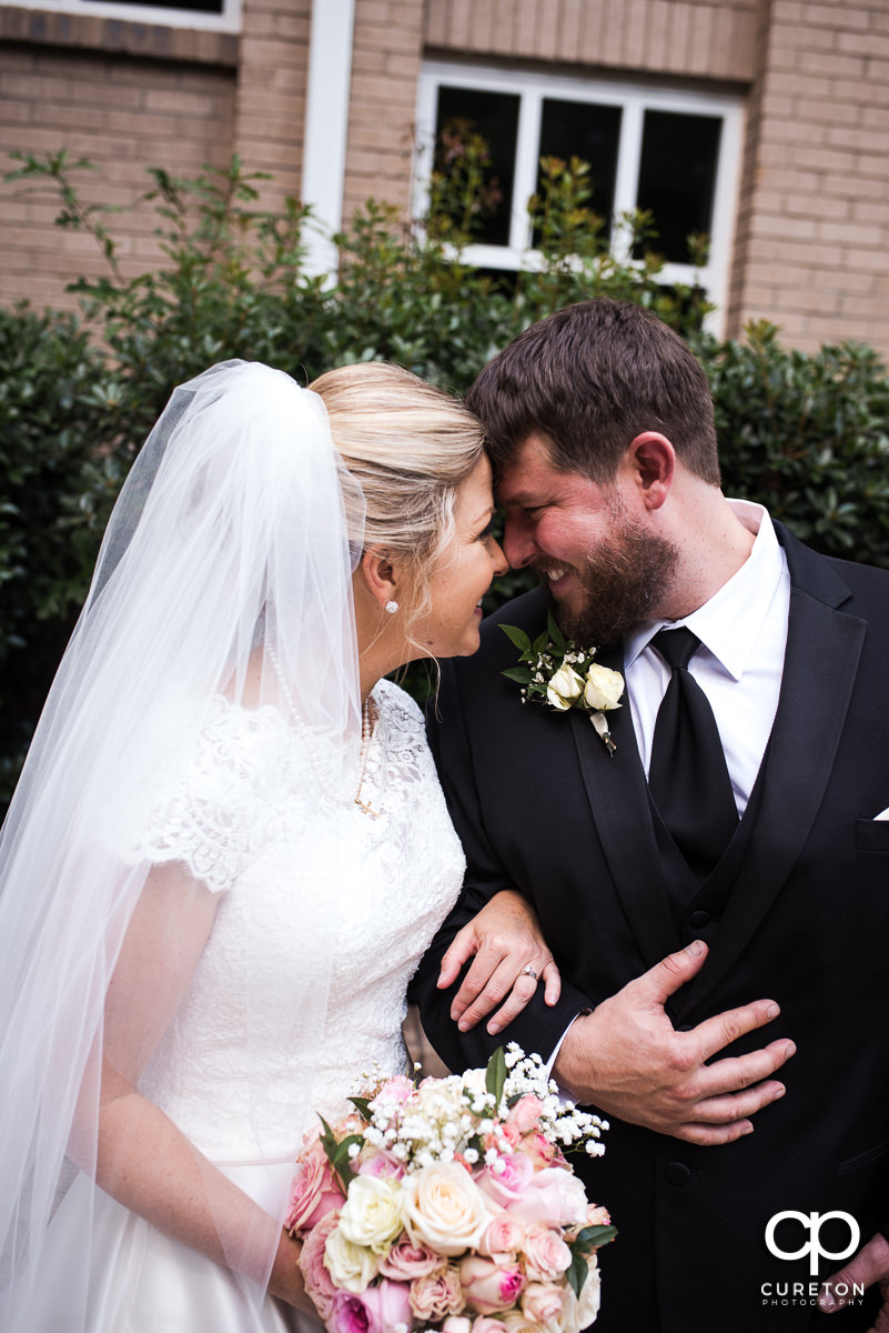 Bride and groom nose to nose after their church wedding.