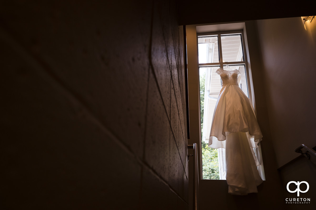 Bride's dress hanging in a church window.