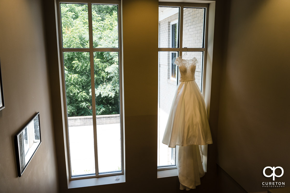 Bride's dress hangin in a church window.