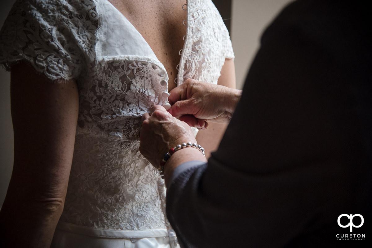 Bride fastening her dress.