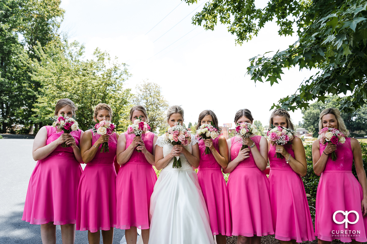 Bride and bridesmaids holding flowers over their faces.