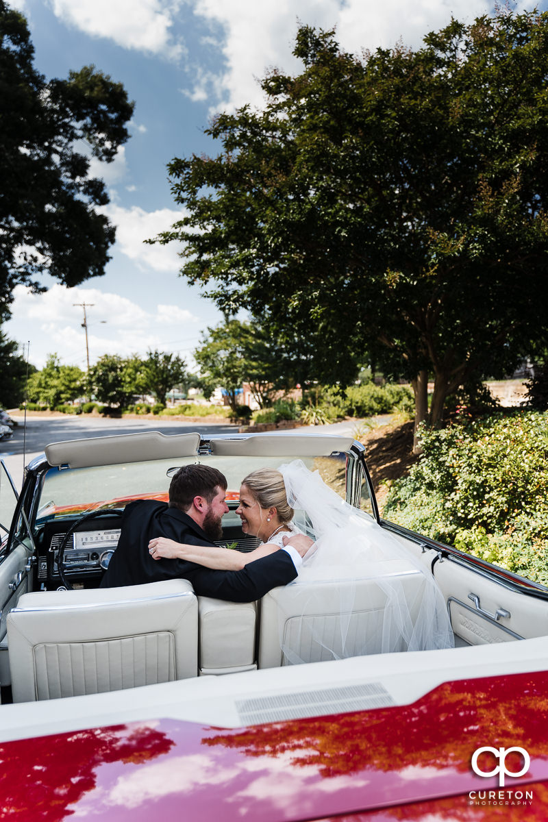 Bride and groom preparing tp leave the church in a classic Lincoln.