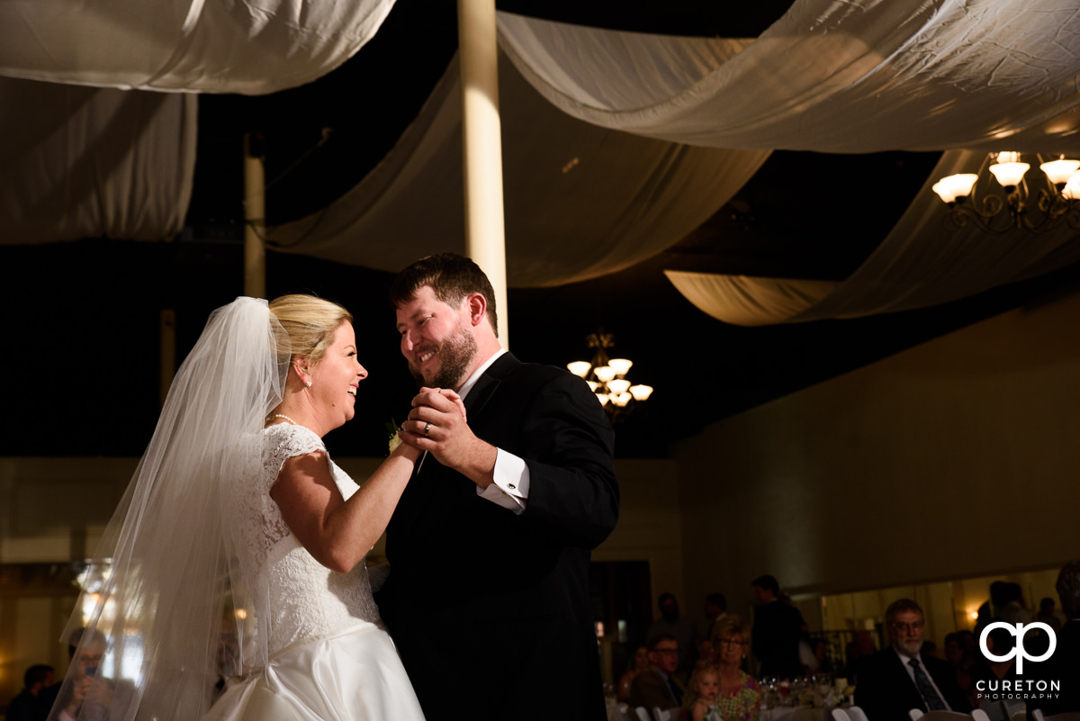 Groom smiling at his bride as they share a first dance at their Grace Hall wedding reception in downtown Greer,SC.