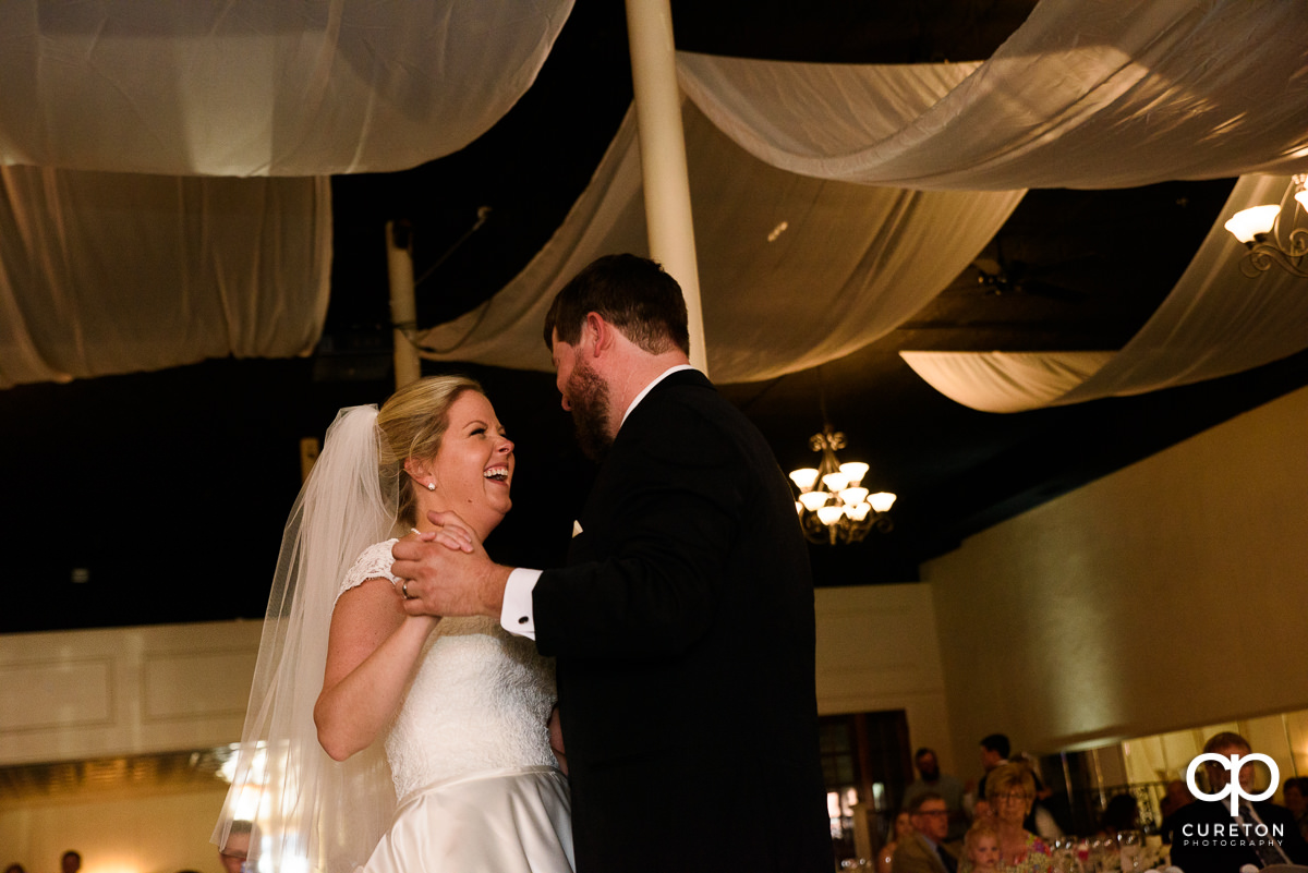 Bride laughing during their first dance at their Grace Hall wedding reception in downtown Greer,SC.