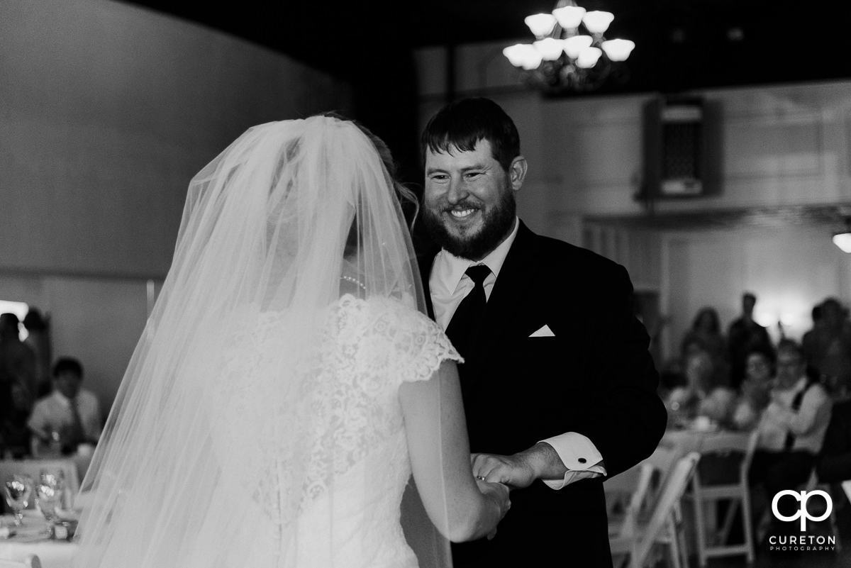 Groom smiling at his bride during a first dance at their Grace Hall wedding reception in downtown Greer,SC.