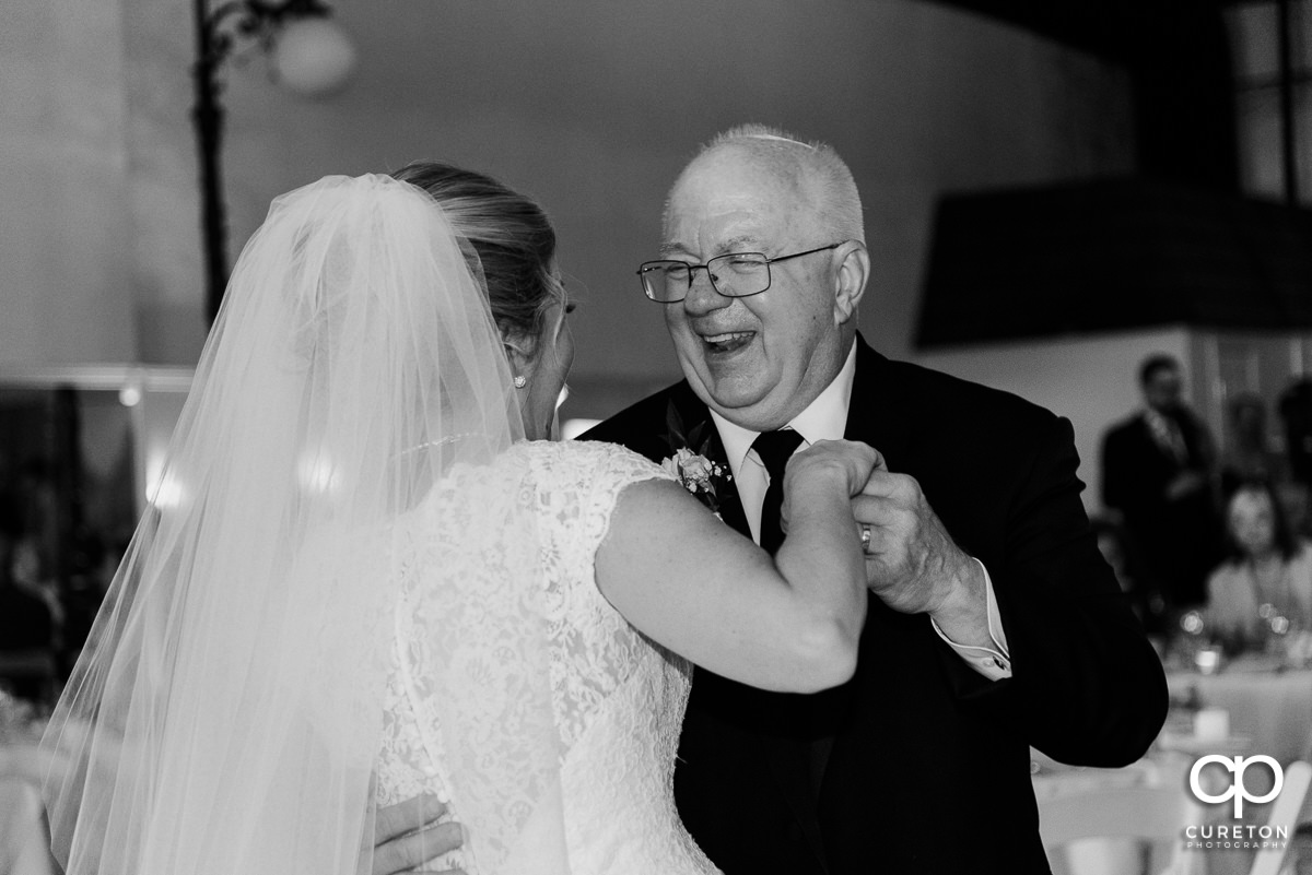 Bride's dad smiling during the first dance with his daughter at the Grace Hall wedding reception in downtown Greer,SC.