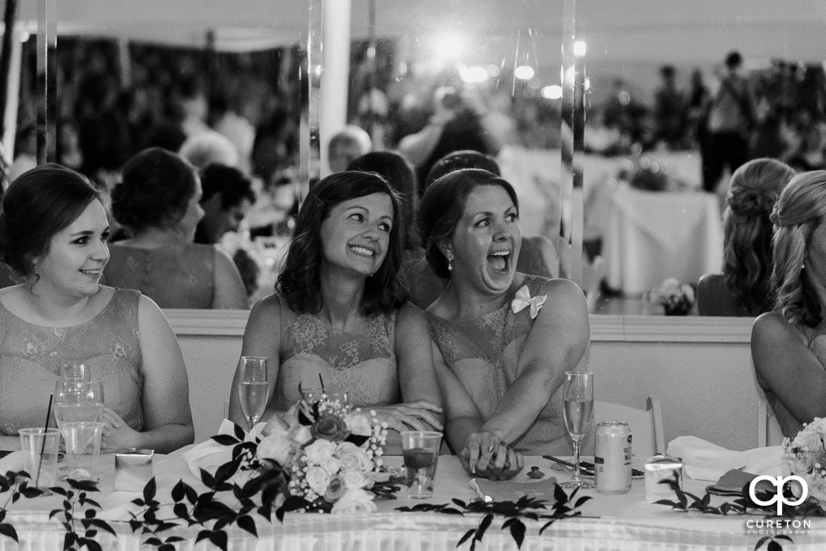 Bridesmaids smiling while watching the newlyweds dance.