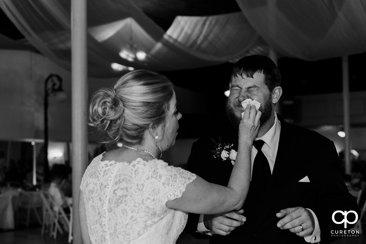 Bride wiping cake off of the groom's face.