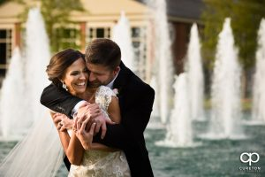 Bride smiling as her groom hugs her from behind in front of a row of fountains.