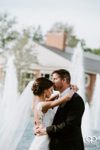 Groom kissing his bride on the forehead on the Furman University campus after their wedding ceremony.