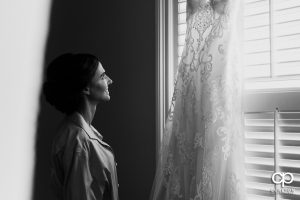 Bride looking at her dress hanging in the window.