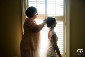 Bride's mother putting in her veil before the ceremony.