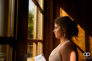 Bridesmaid staring out of a window of the chapel.