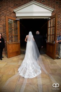 Bride walking into the chapel with her father.