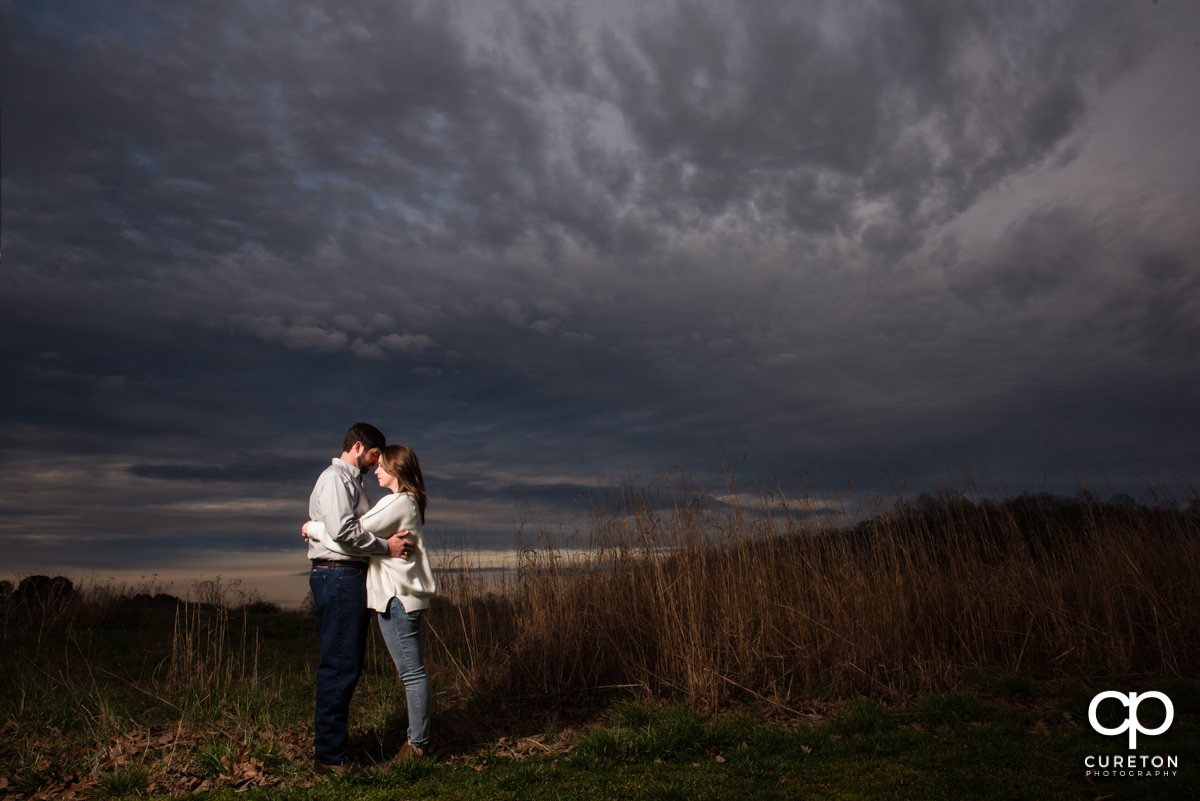 Engaged couple standing in a field at sunset during an engagement session at Greenbrier Farms.