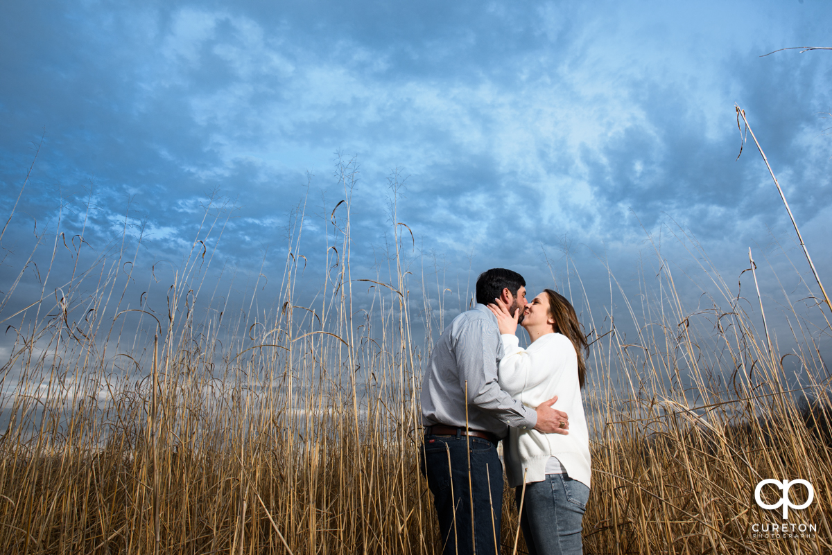 Engaged couple standing in a field of tall grass during an engagement session at Greenbrier Farms in Easley SC.