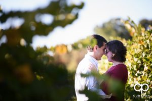 Engaged couple snuggling during their rustic engagement session near Greenville South Carolina.
