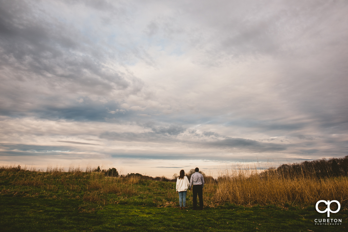 Engaged couple holding hands in a field.