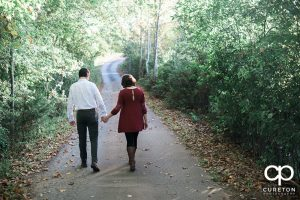 Couple walking down the road during their engagement session on a farm near Greenville South Carolina.