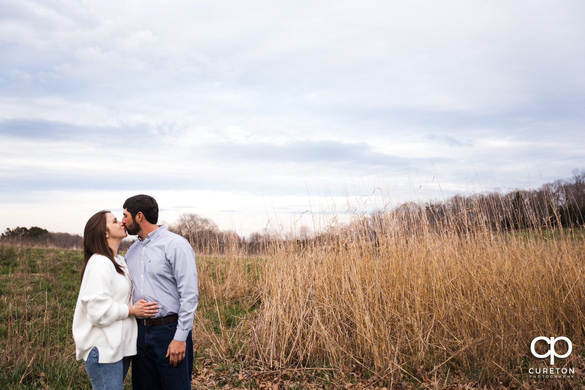 Engaged couple kissing in a field of tall grass.