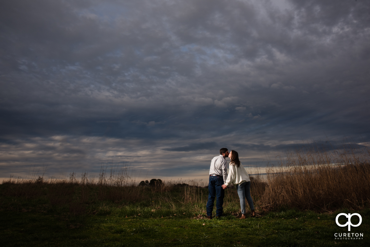 Couple kissing in a field at sunset at Greenbrier Farms.