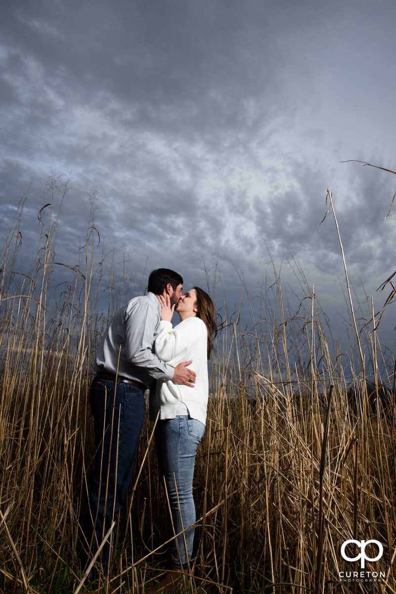 Engaged couple snuggling in a field during an engagement session.