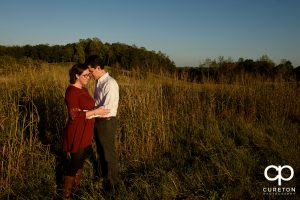 Future bride and groom standing in a field during their engagement session.