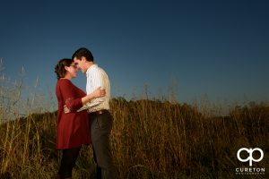 Bride and groom hugging during their engagement session in the middle of the field.