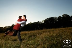 Groom lifting his bride in a field during their engagement session.