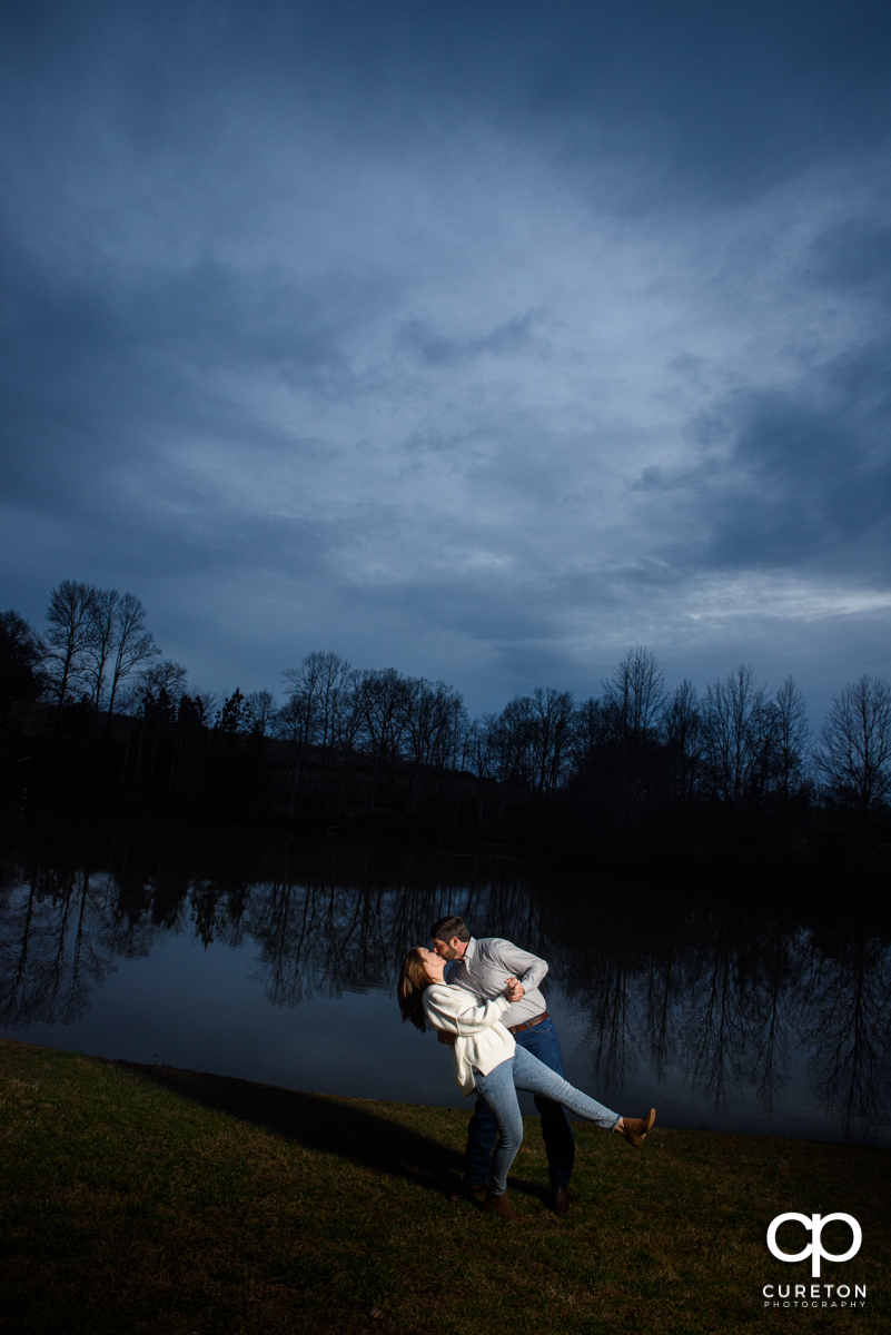 Man dipping his fiancee in front of a lake.
