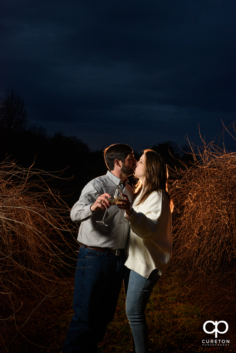 Engaged toasting some champagne in the vineyard at Greenbrier Farms during an engagement session.