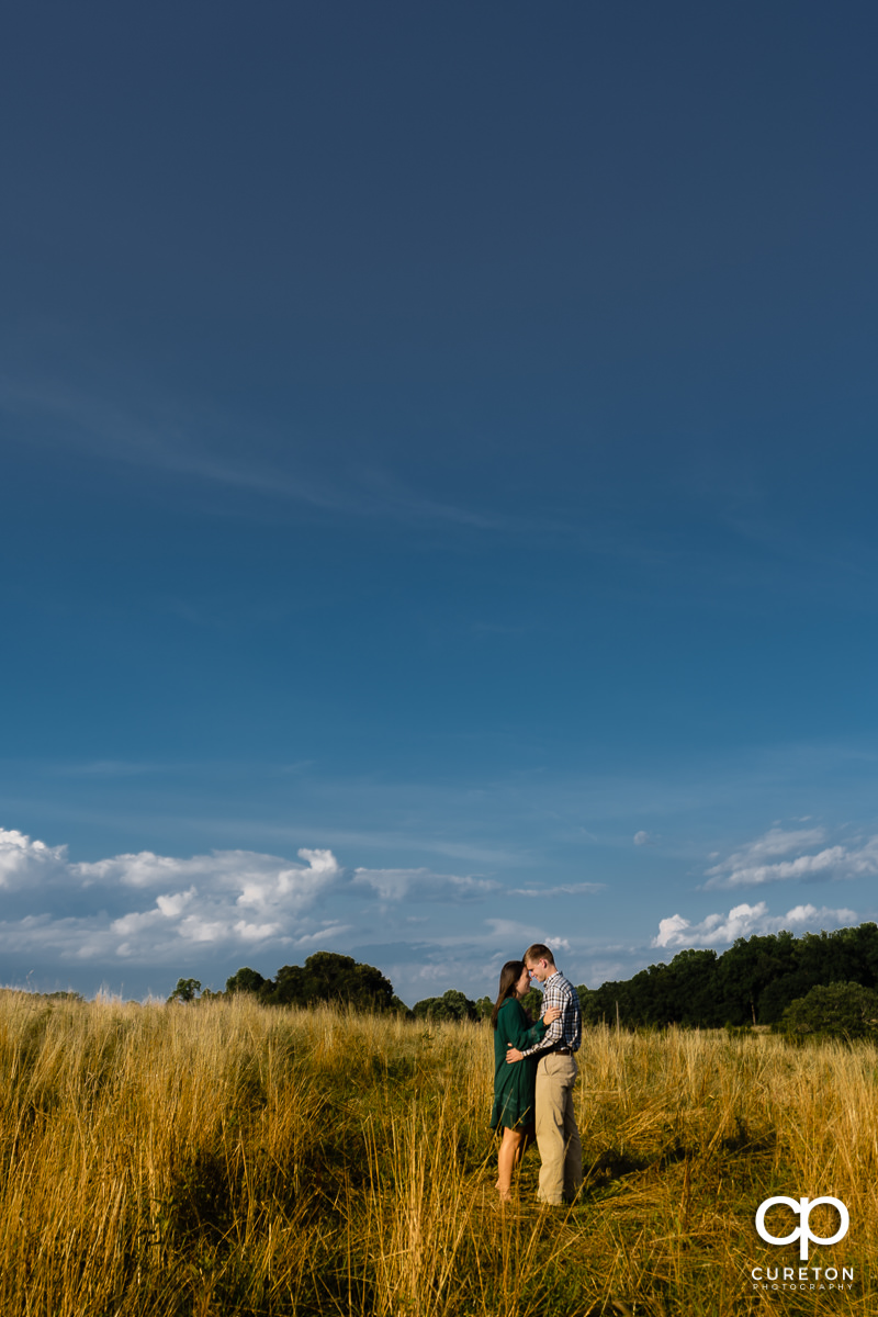 Engaged couple hugging in a field during their engagement session at Greenbrier Farms in Easley,SC.