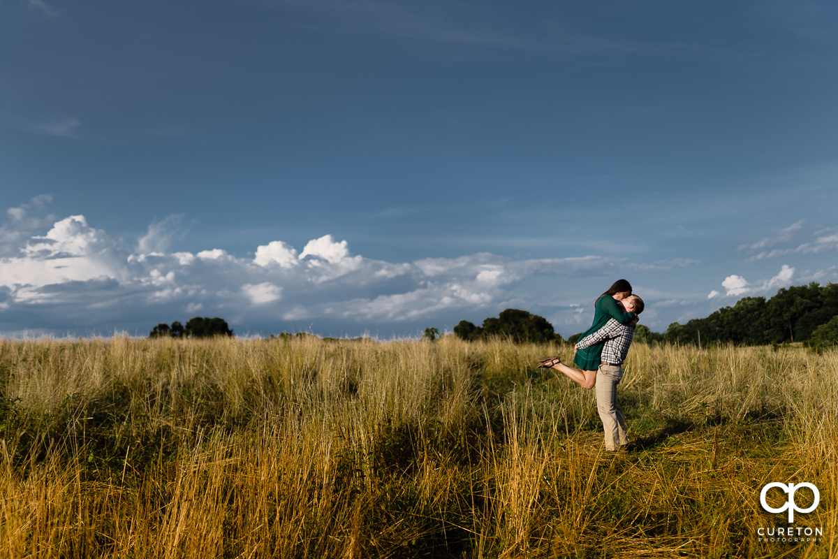 Man lifting his fiancee in a open field of tall grass during their engagement session at Greenbrier Farms in Easley,SC.