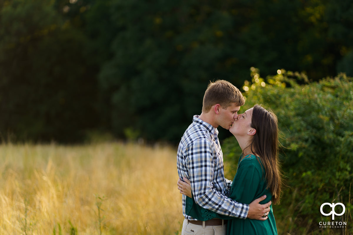 Man kissing his fiancee in a field.