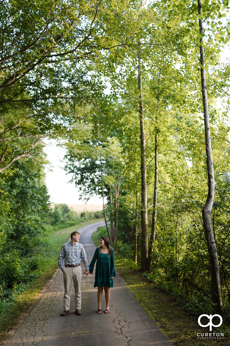 Engaged couple walking down a path.