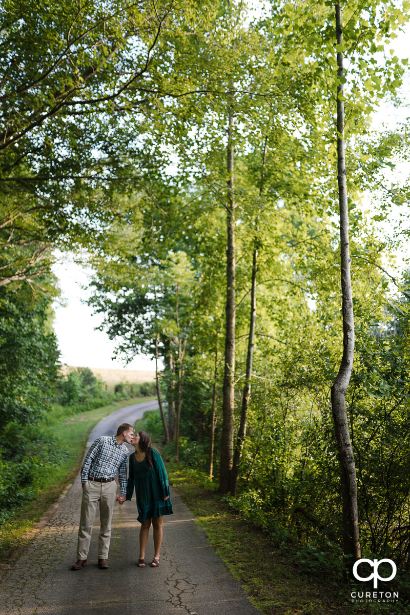 Engaged couple stopping for a kiss as they walk down a tree covered path.