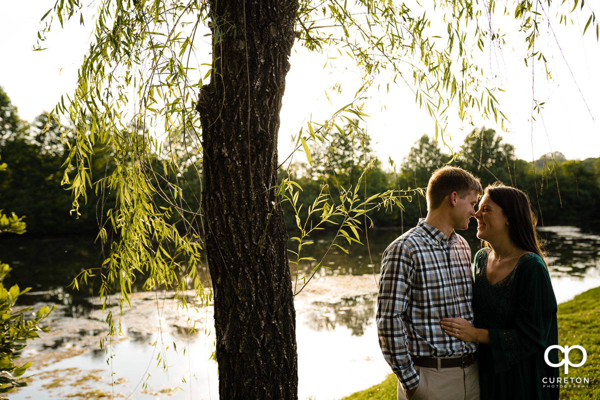 Man and his fiancee walking by a pond.