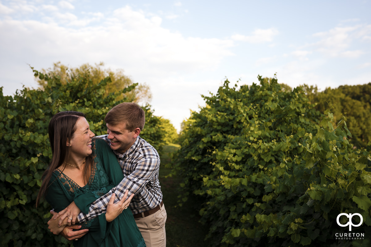 Engaged couple laughing together in a vineyard at Greenbrier Farms.
