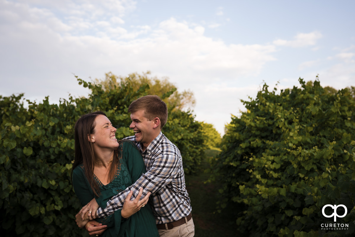Engaged couple laughing together in a vineyard.