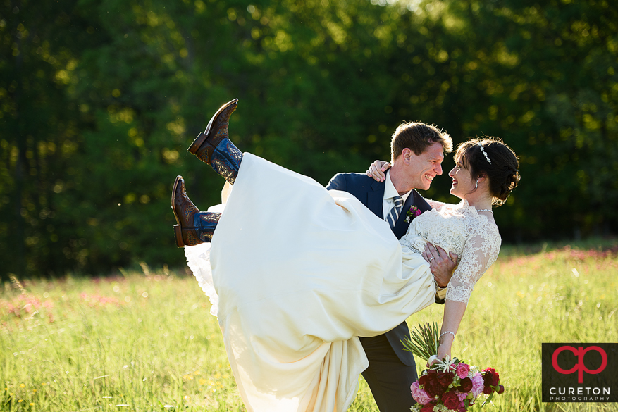 Husband carrying his wife after their Greenbrier Farms wedding.