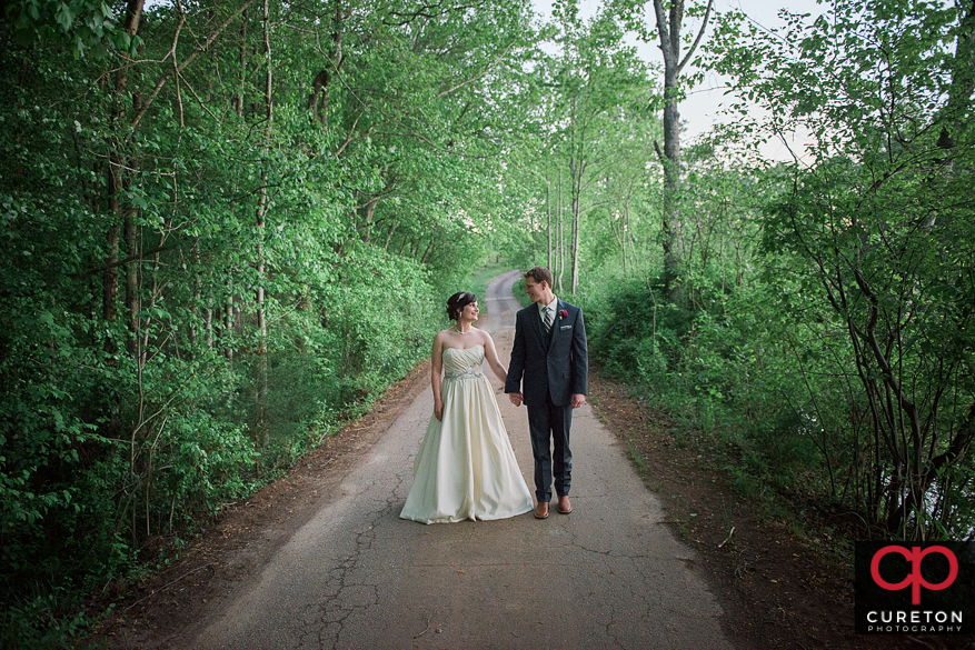 Bride and groom strolling down the road their Greenbrier Farms wedding.