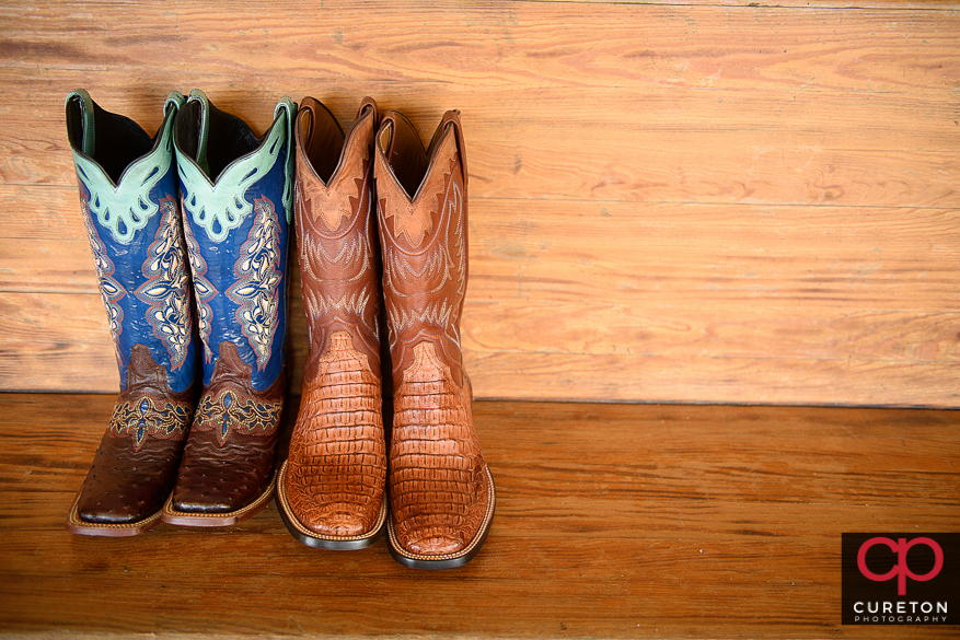 Bride's cowboy boots next to the grooms boots.