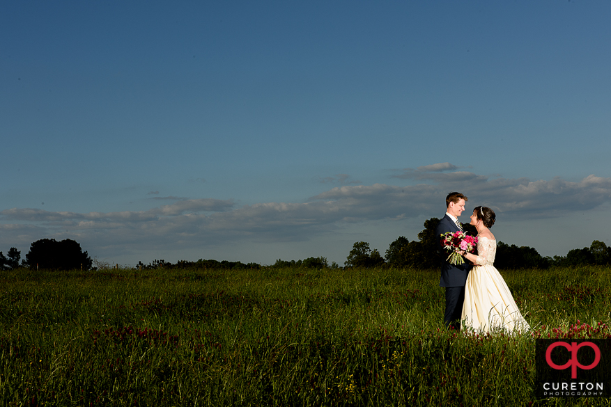 Bride and groom in a field on the far.