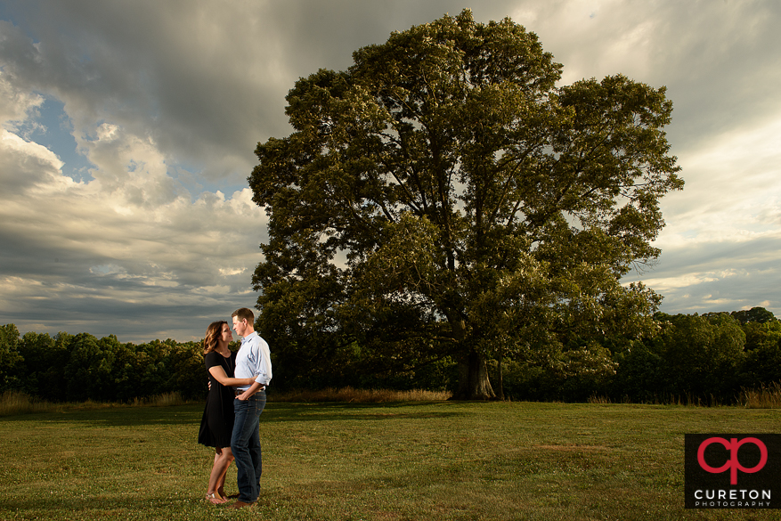 Future bride and groom kissing by the oak tree during a Greenbrier Farms Engagement Session.