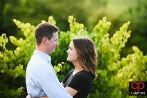Engaged couple walking though a farm vineyard.