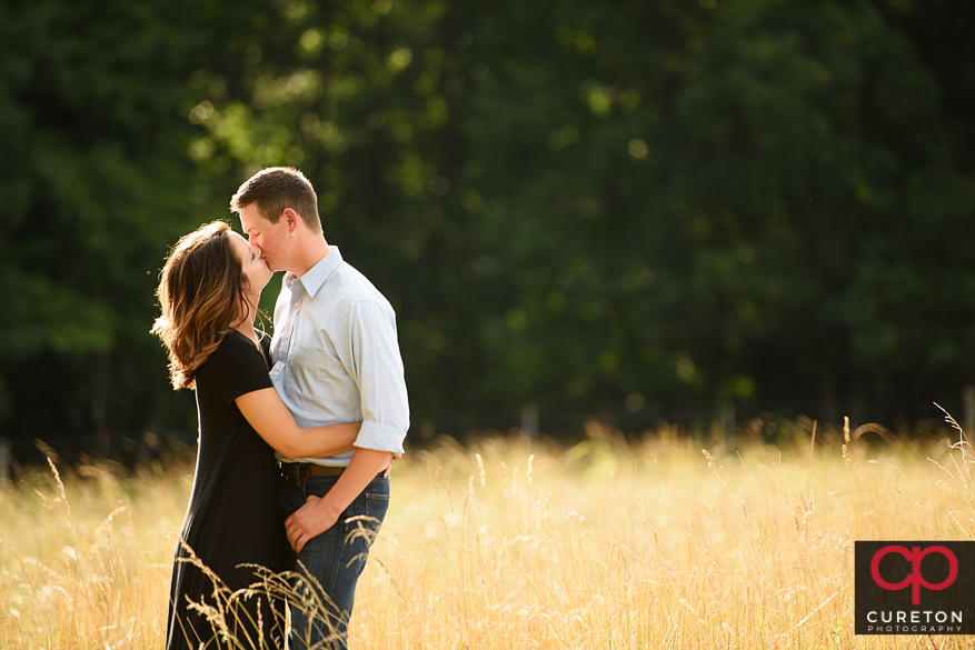 Future bride and groom kissing in a field of tall grass.