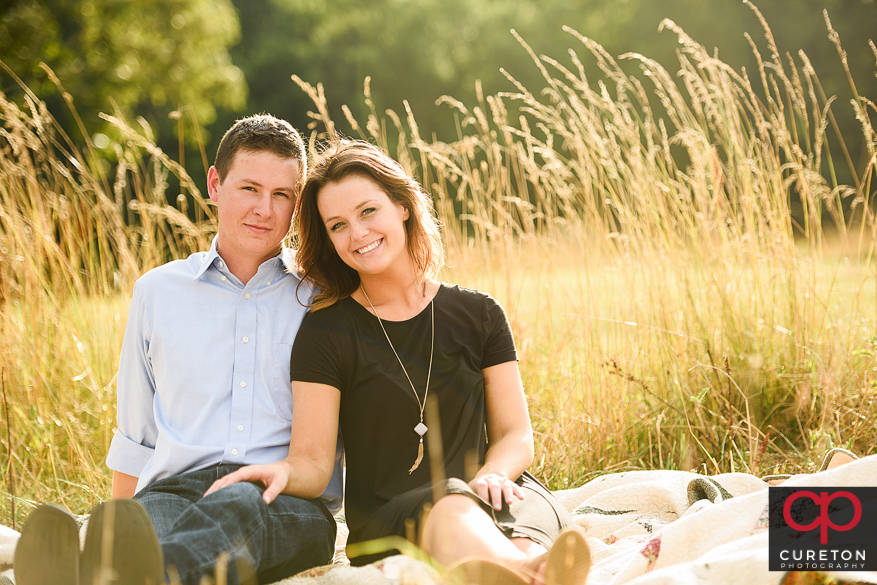 Engaged couple sitting in a field of tall grass.