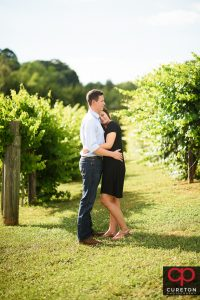 Couple snuggling on a farm during a rustic engagement session.