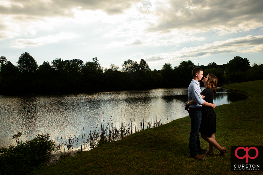 Engaged couple dancing by the lake at Greenbrier Farms.